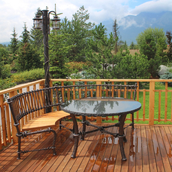 Stĺpové kované svietidlo a kované posedenie z UKOVMI na terase chalupy v tatranskom prostredí - záhradné svietidlo