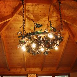 Ručne kovaný dubový luster v letnom altánku - štýlové osvetlenie s motívom prírody - luxusný luster