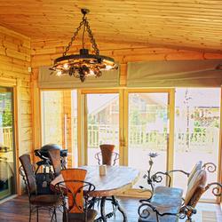 Luxusné závesné svietidlo v uzavretom altánku horskej chalupy - nábytok v kovanom štýle