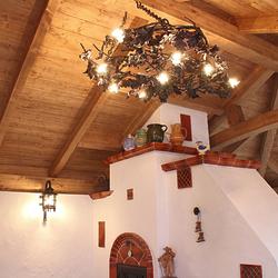 Štýlový luster s prírodným motívom v uzavretom letnom altánku s kuchyňou vo vidieckom štýle