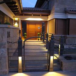 Celkový pohľad na vstup k rodinnému domu osvietený ručne kovanými svietidlami z UKOVMI