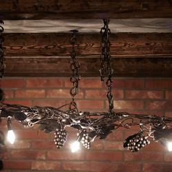 Umelecké ručne kované svietidlo na reťazi navrhnuté ako originálne svietidlo pre vínnu pivnicu
